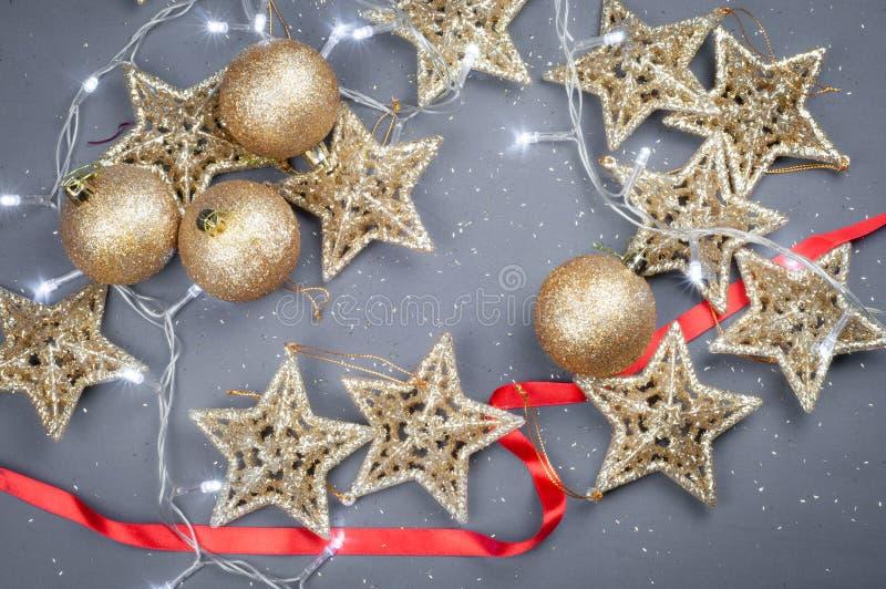 Stelle e palle dorate dei giocattoli di Natale su un fondo grigio fotografia stock libera da diritti
