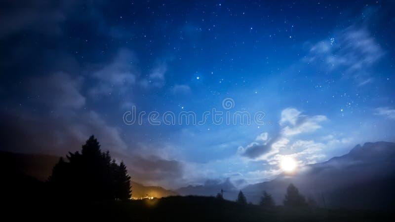 Stelle, luna e nuvole del cielo notturno attraverso la montagna fotografia stock libera da diritti