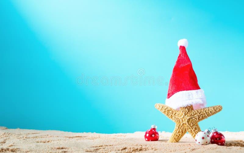 Stelle marine con il cappello di Santa sulla spiaggia con gli ornamenti di Natale immagini stock libere da diritti