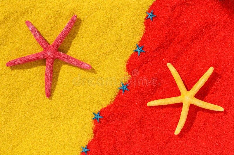 Stelle marine rosse e gialle sulla sabbia di colore immagini stock