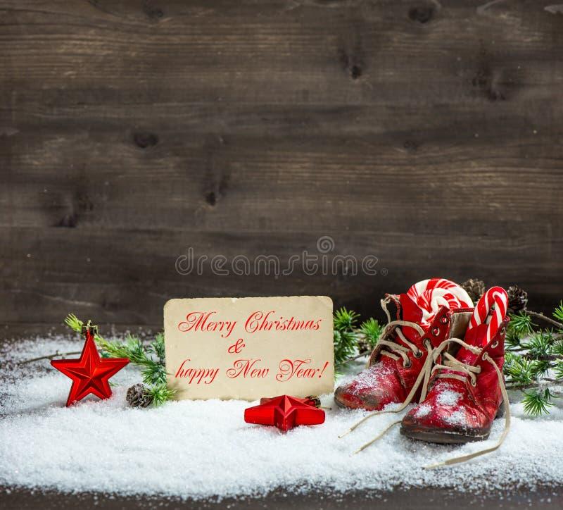 Stelle rosse della decorazione di Natale e scarpe di bambino antiche in neve fotografie stock libere da diritti