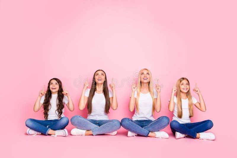 Stellen de aantrekkelijke vrolijke vrolijke blije zekere lange het haarmeisjes die van Nice op vloer in lotusbloem zitten positie royalty-vrije stock afbeelding