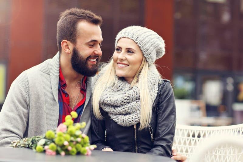 Stellen Sie das Zeigen von jungen Paaren mit den Blumen dar, die in der Stadt datieren lizenzfreies stockbild