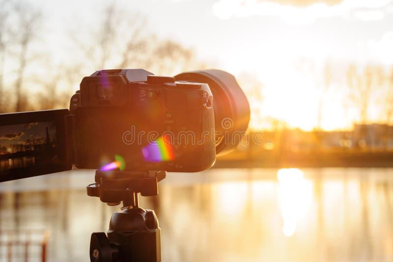 Stellen Sie die Kamera auf einem Stativ ein, um Zeitraffervideo des Sonnenuntergangs zu notieren stockfotografie
