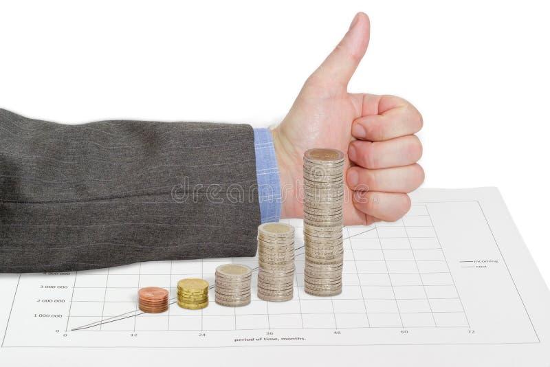 Stellen Sie grafisch dar, errichtet von den Münzen auf dem Hintergrund der anerkennend Geste stockfotos