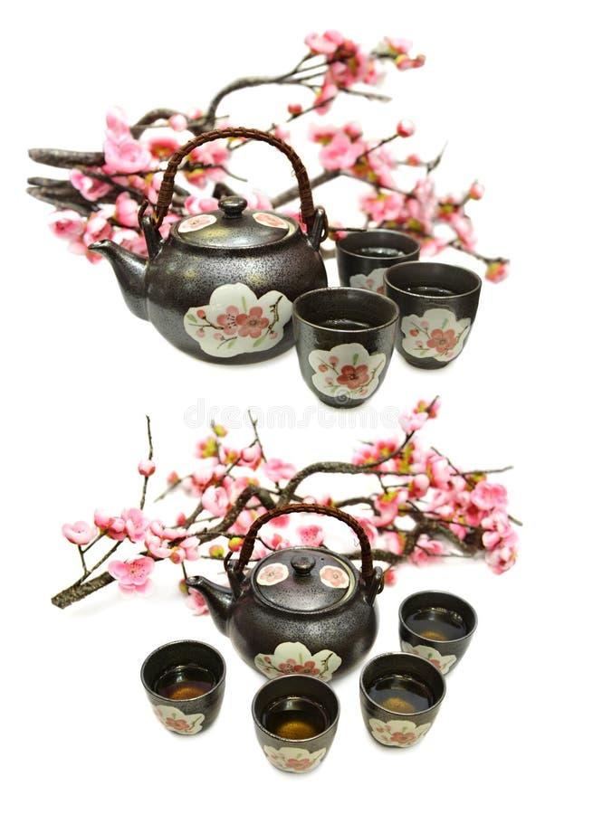 Stellen Sie mit Topf des schwarzen Tees und Kirschblüte-Niederlassung ein stockfoto