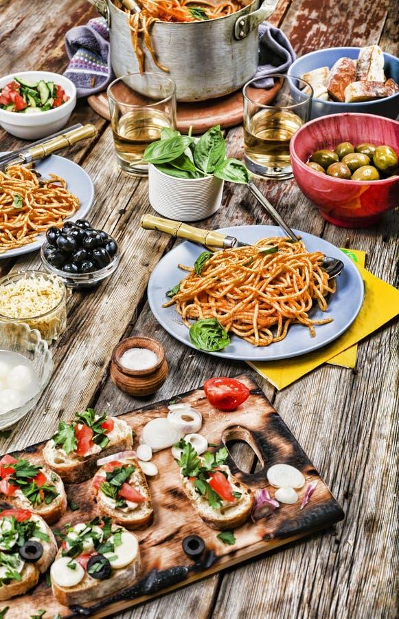 Stellen Sie mit traditionellem italienischem Lebensmittel ein Konzept: Italienisches Abendessen mit Wein und Spaghettis stockfotos