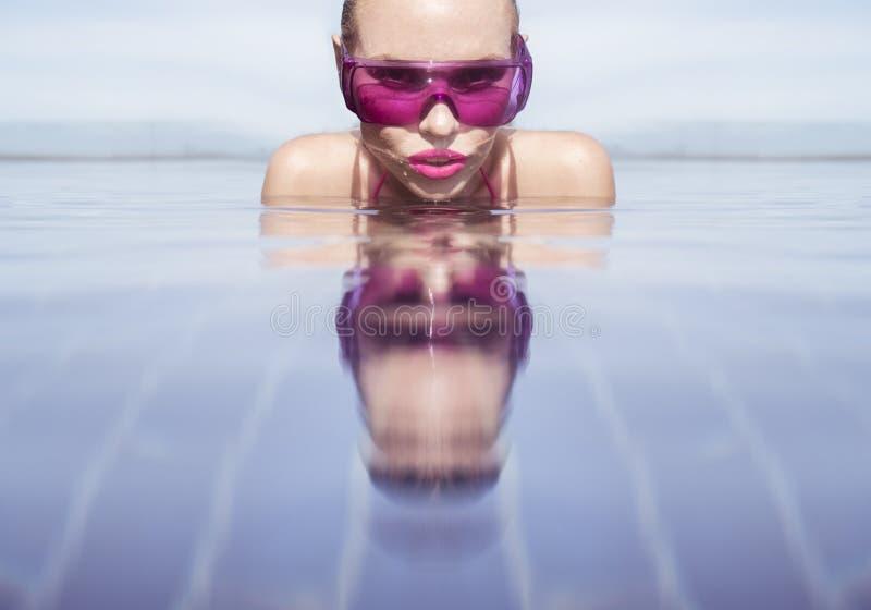 Stellen Sie Nahaufnahme der Frau in der purpurroten Sonnenbrille im Unendlichkeitsdachspitzen-Swimmingpool gegenüber lizenzfreie stockfotos