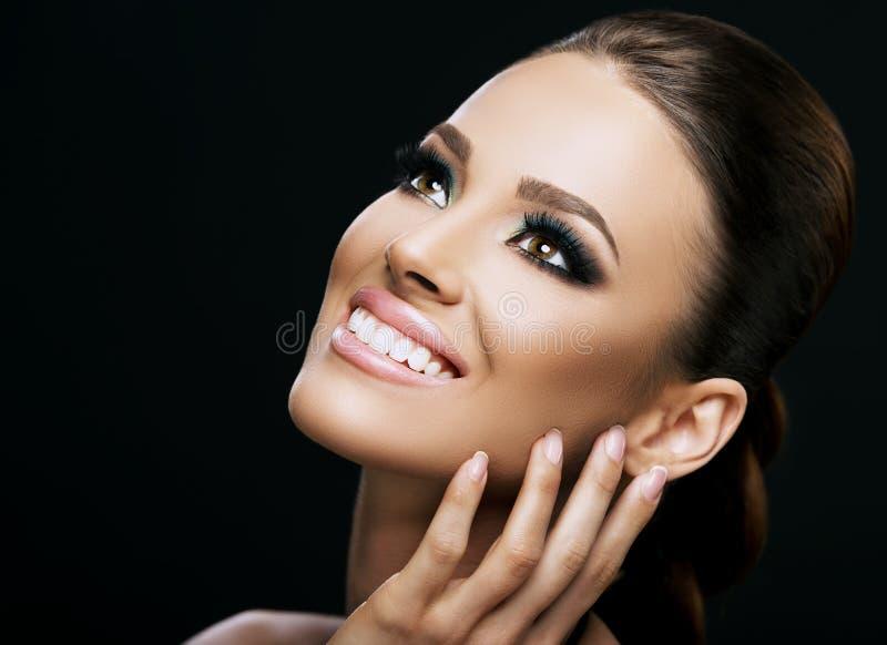 Stellen Sie Nahaufnahme einer schönen jungen Frau gegenüber, die auf dunklem Hintergrund lokalisiert wird; vervollkommnen Sie Hau stockfoto
