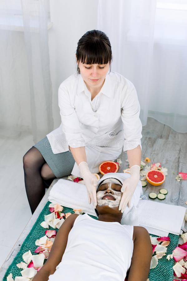 Stellen Sie Schalenmaske, Badekurortsch?nheitsbehandlung, skincare gegen?ber Hübsche Afrikanerin, die Gesichtspflege durch Kosmet stockfoto