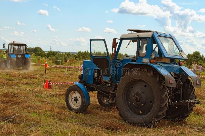 Stellen Sie steuernden Wettbewerb am Feld dar Blauer alter Traktor wartet auf es Versuch Folgender Teilnehmer ist bereit zu begin stockbild