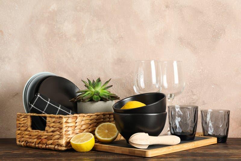 Stellen Sie vom Essgeschirr mit saftiger Anlage und Zitronen auf Holztisch ein stockfoto