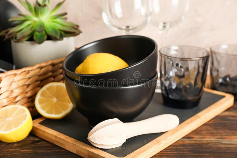 Stellen Sie vom Essgeschirr mit saftiger Anlage und Zitronen auf Holztisch ein stockfotografie