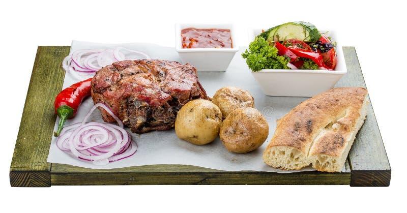 Stellen Sie vom Schweinefleischsteak, vom Gem?sesalat, von den Kartoffeln und von der So?e ein Chalagach lizenzfreie stockfotos