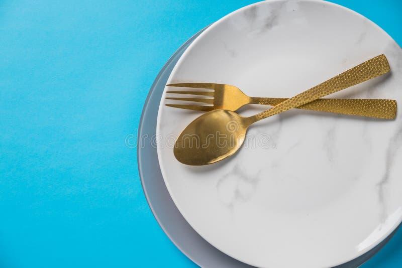 Stellen Sie vom Tischbestecklöffel, Gabel, die Platte ein, lokalisiert auf blauem Hintergrund Wei?e Marmorplatte Beschneidungspfa stockfotos