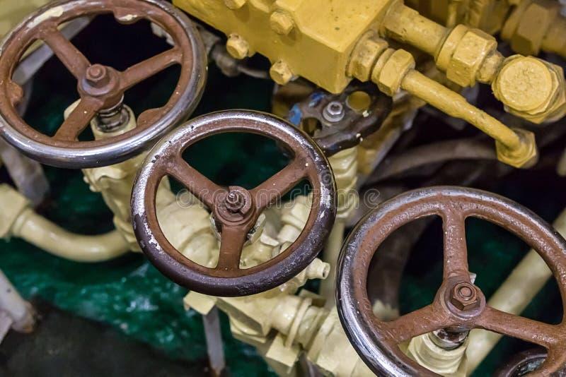Stellen Sie von den alten schäbigen runden Ventilventilen auf einem Hintergrund des Rohrventilteils Ausrüstungsunterseebootinfras stockbild