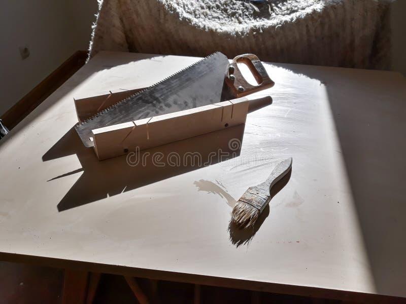 Stellen Sie von den Arbeitswerkzeugen auf Tabelle ein: Säge, Bördelmaschine und painter& x27; s-Bürste lizenzfreie stockbilder