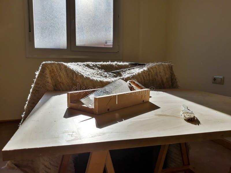 Stellen Sie von den Arbeitswerkzeugen auf Tabelle ein: Säge, Bördelmaschine und painter& x27; s-Bürste stockfoto