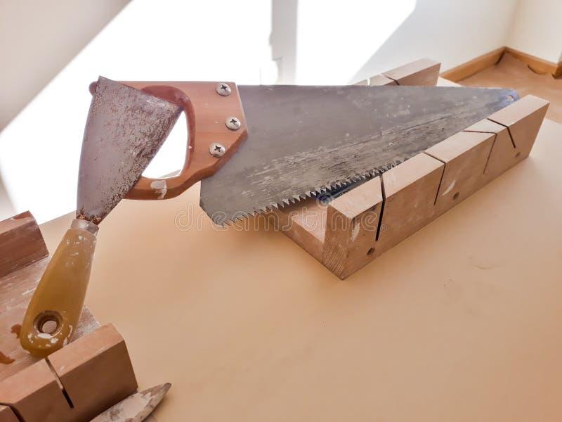 Stellen Sie von den Arbeitswerkzeugen auf Tabelle ein: Säge, Bördelmaschine und painter& x27; s-Bürste stockfotos