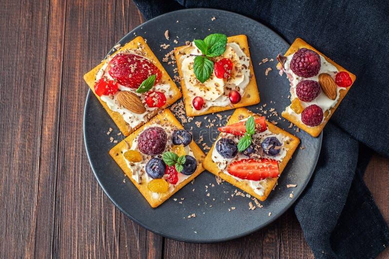 Stellen Sie von den Crackern mit verschiedener Fruchtnahaufnahme auf dunklem Holztisch ein Beschneidungspfad eingeschlossen lizenzfreie stockfotografie