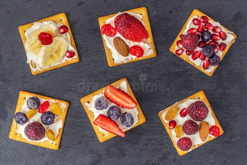 Stellen Sie von den Crackern mit verschiedener Fruchtnahaufnahme auf dunkler Schieferplatte ein Beschneidungspfad eingeschlossen stockfoto