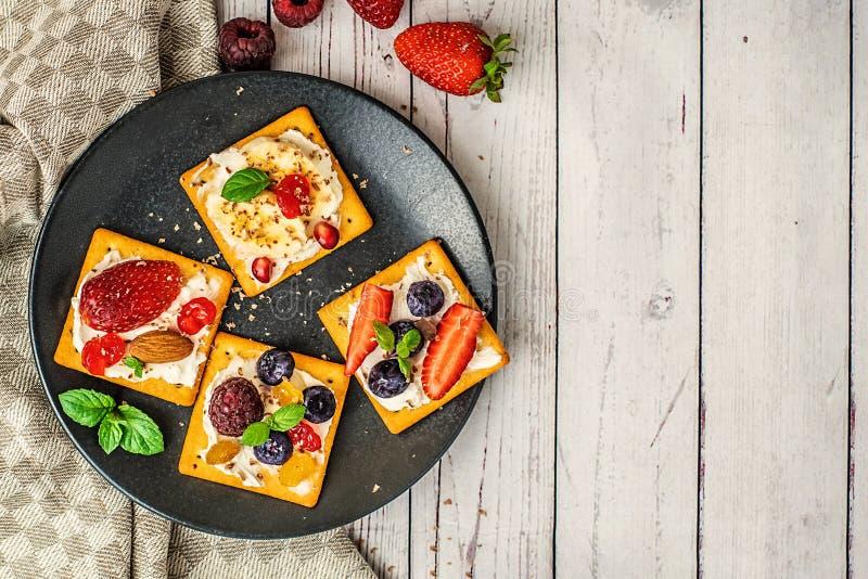 Stellen Sie von den Crackern mit verschiedener Fruchtnahaufnahme auf hellem hölzernem Hintergrund ein Draufsicht, mit Kopienraum lizenzfreie stockfotografie