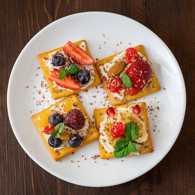 Stellen Sie von den Crackern mit verschiedener Fruchtnahaufnahme auf weißer Platte ein Beschneidungspfad eingeschlossen stockfotos