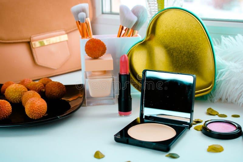 Stellen Sie von den dekorativen Kosmetik mit Pulverpaletten-, -lippenstift-, -parfume- und -Litschifrüchten ein Weibliches Zauber lizenzfreie stockfotografie