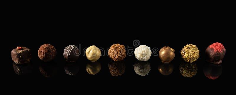 Stellen Sie von den feinen Pralinen weiße, Dunkle und Milchschokolade auf schwarzem Hintergrund mit Reflexion ein lizenzfreies stockfoto
