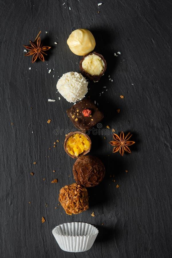 Stellen Sie von den feinen Pralinen wei?e, Dunkle und Milchschokolade auf schwarzem Hintergrund, Draufsicht ein stockbilder