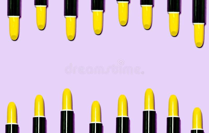 Stellen Sie von den gelben Lippenstiften ein, die auf hellpurpurnem Farbhintergrund lokalisiert werden lizenzfreie stockbilder