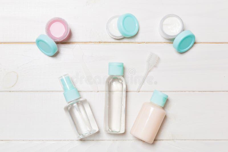 Stellen Sie von den kosmetischen Flaschen der Reisegröße auf weißem hölzernem Hintergrund ein Flache Lage von Cremetiegeln Draufs lizenzfreie stockfotografie