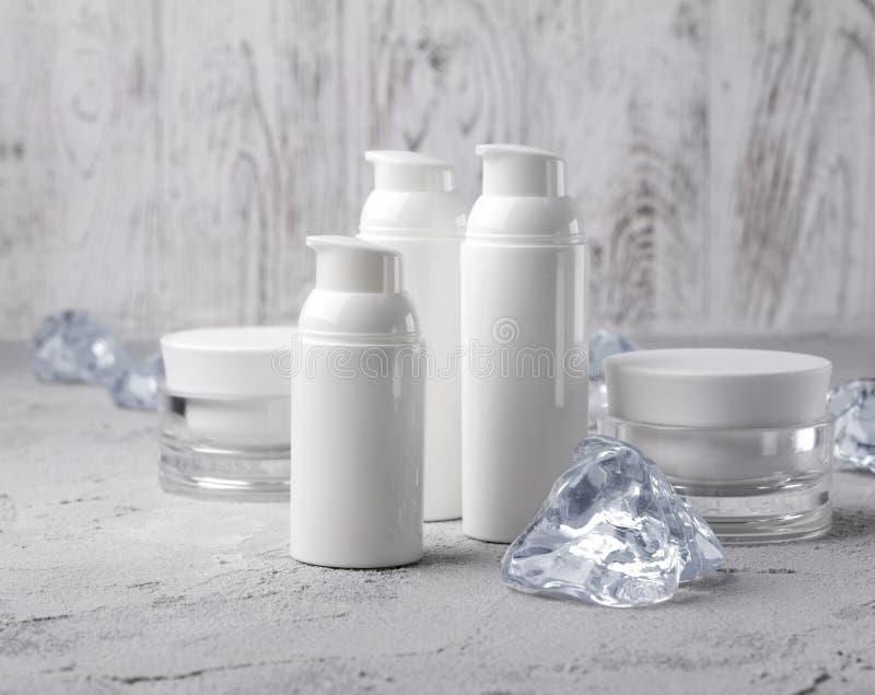 Stellen Sie von den kosmetischen Sahneflaschen mit Eis auf grauer Tabelle ein lizenzfreie stockfotografie
