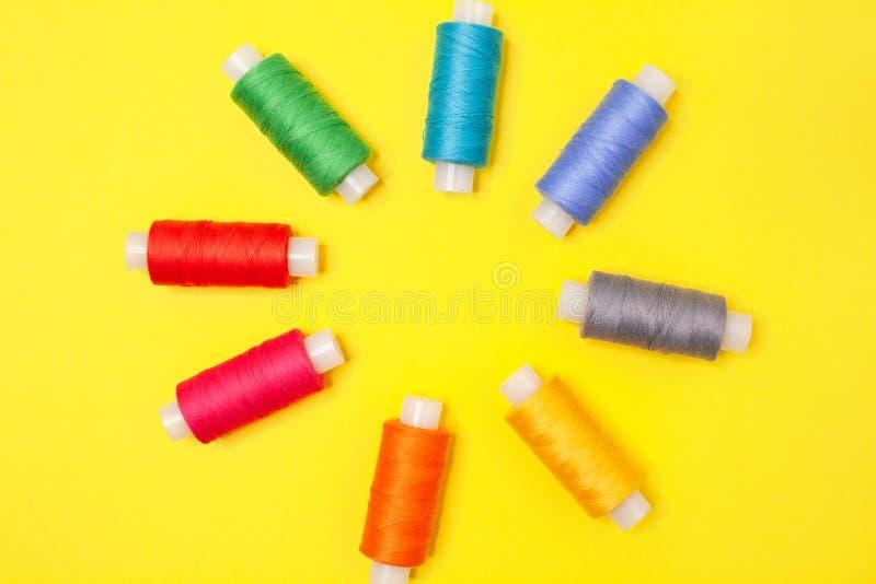 Stellen Sie von den mehrfarbigen Spulen des Fadens auf gelbem Hintergrund ein Zusätze für Näharbeit, Stickerei, nähend Flache Lag lizenzfreie stockbilder
