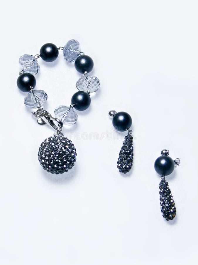 Stellen Sie von den Ohrringen und von einem Armband mit blauen Edelsteinsteinen und vom Diamanten, der Edelsteine schaut ein stockfotografie