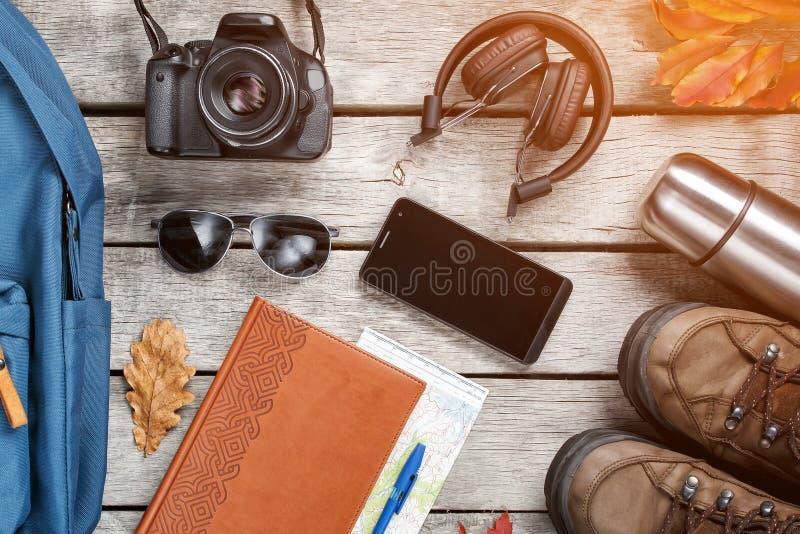 Stellen Sie von den Sachen und von der touristischen Ausr?stung f?r Reise und Abenteuer auf einem grauen h?lzernen Hintergrund ei stockbild