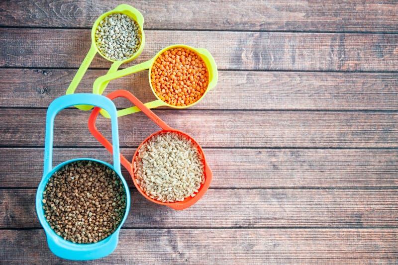 Stellen Sie von den verschiedenen Getreide in den mehrfarbigen Behältern, im Hafermehlbuchweizen, in der Gerste und im Reis ein lizenzfreie stockbilder