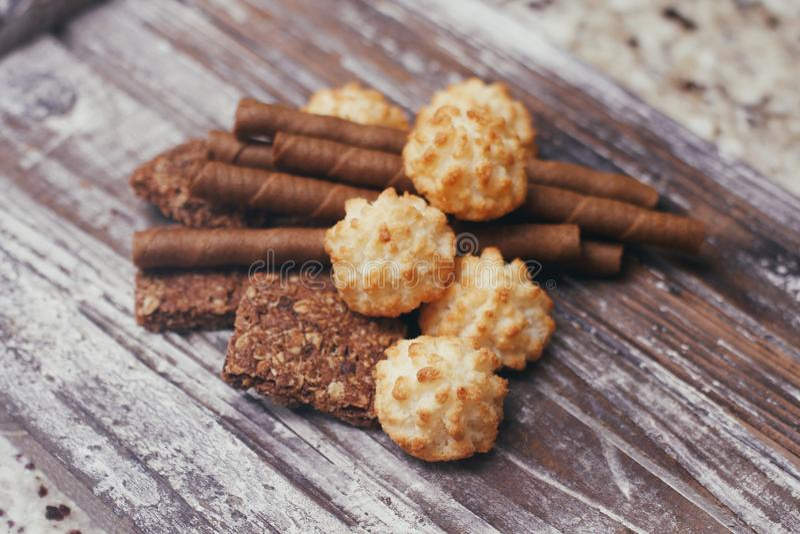 Stellen Sie von den verschiedenen Süßigkeitenbonbons auf Holztisch ein Schokolade, Waffeln, Kokosnusskekse, Plätzchen stockfoto