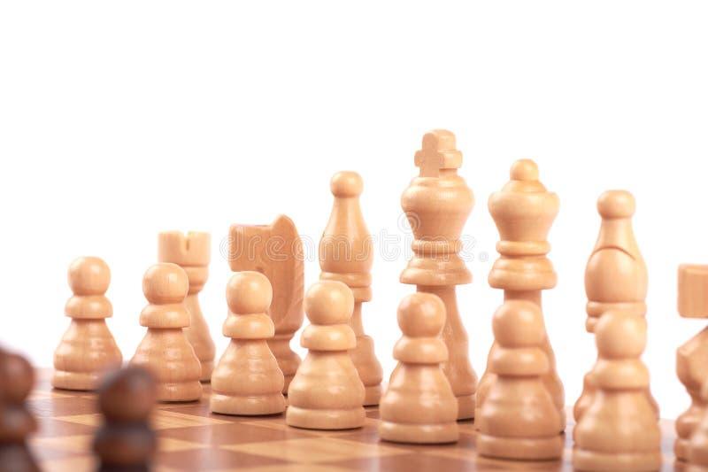 Stellen Sie von den weißen und schwarzen hölzernen Schachfiguren ein, die auf einem Schachbrett stehen, lokalisiert auf weißem Hi lizenzfreies stockfoto