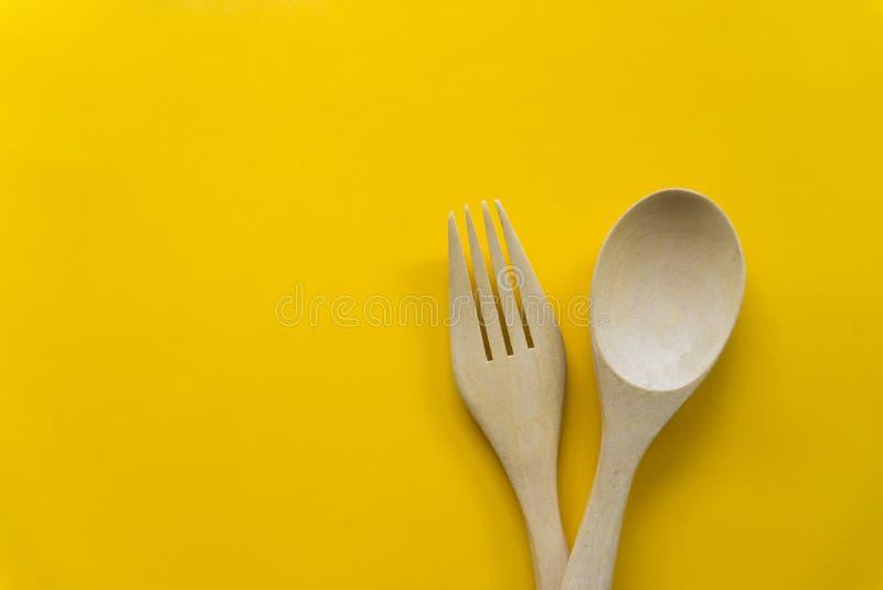 Stellen Sie von der Gabel, vom L?ffel und vom Tellerholz mit gelbem Hintergrund ein stockfoto