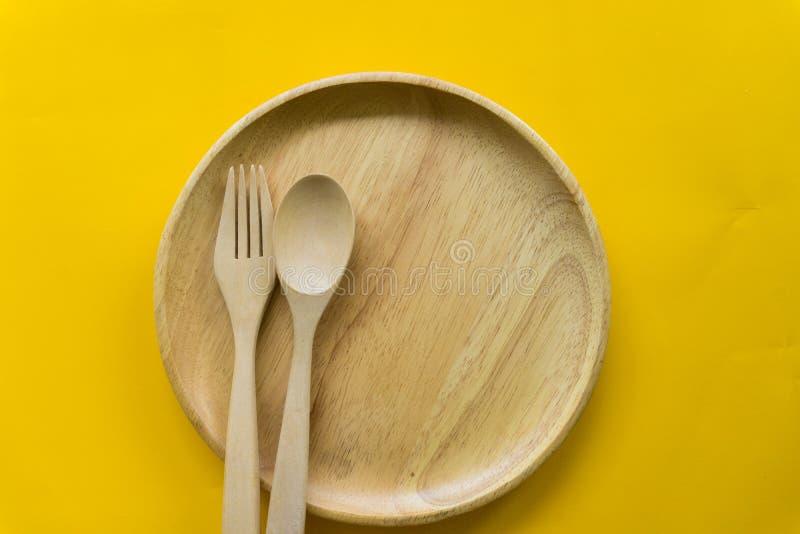 Stellen Sie von der Gabel, vom L?ffel und vom Tellerholz mit gelbem Hintergrund ein lizenzfreie stockbilder
