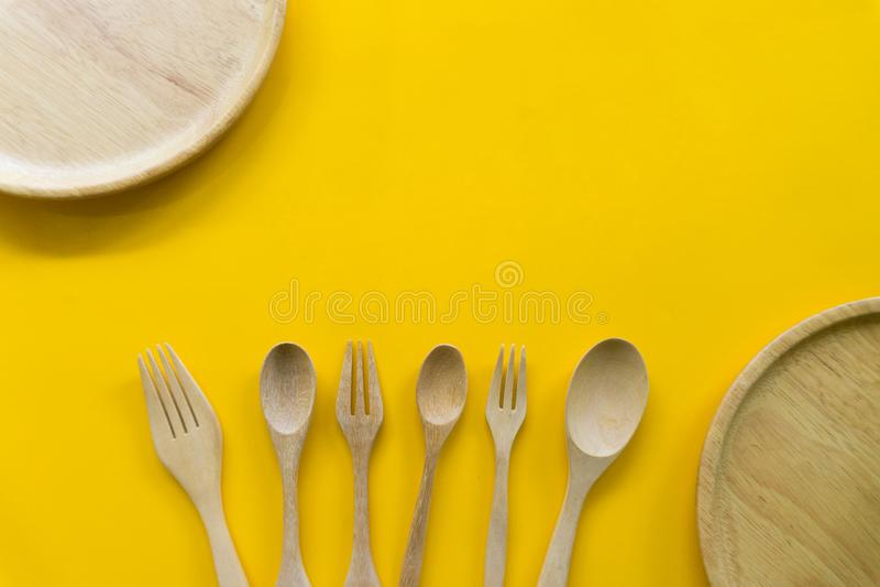 Stellen Sie von der Gabel, vom L?ffel und vom Tellerholz mit gelbem Hintergrund ein stockfotos