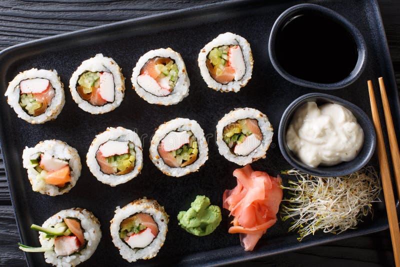 Stellen Sie von der japanischen Rollen-, die uramaki mit Soßen diente, Ingwer- und Wasabinahaufnahme auf dem Tisch ein horizontal stockbilder