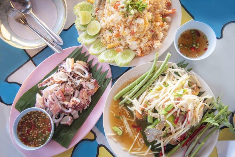 Stellen Sie von der Nahrungsmittelplatte mit gegrilltem Kalmar, Papayasalat, gebratenem Reis und Paprikasoßennahrung von Asien ei lizenzfreie stockbilder
