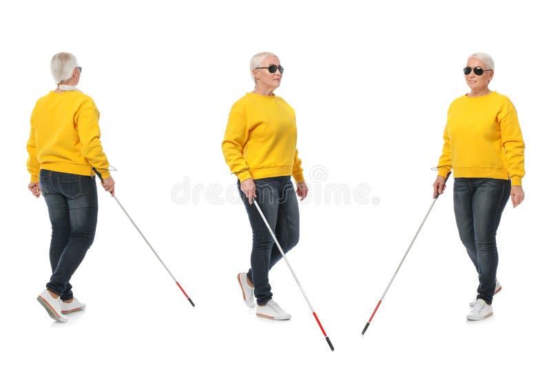 Stellen Sie von der reifen blinden Frau mit langem Stock gehend auf Weiß ein lizenzfreies stockbild