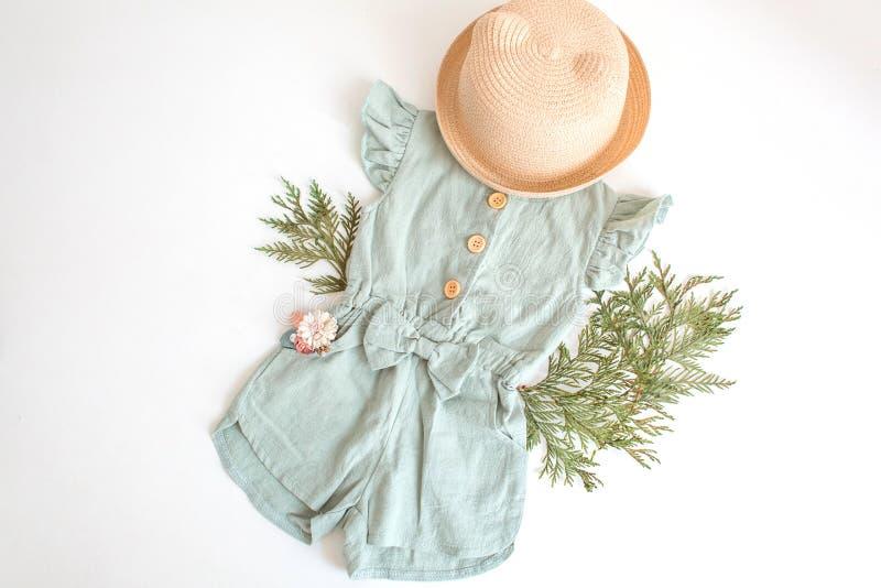 Stellen Sie von der Sommerkinderkleidung für Mädchen ein Lokalisiert, Kopienraum Stilvolle Spielanzugklage, Strohhut und Blumenzu lizenzfreie stockfotografie