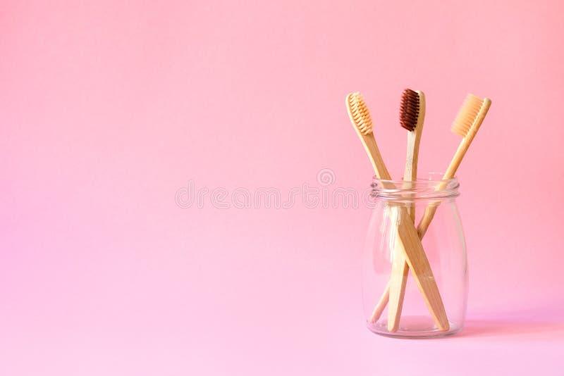 Stellen Sie von drei Bambuszahnbürsten in der Glasflasche, im Zahnpflegen der Familie, im rosa Hintergrund-, umweltfreundlichem u stockfotografie