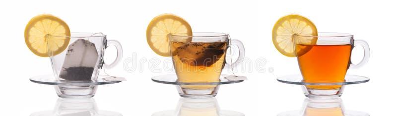 Stellen Sie von drei Teeschalen mit Zitronenscheibe ein und der Teebeutel, der auf weißem Hintergrund lokalisiert wird, machen e lizenzfreies stockfoto