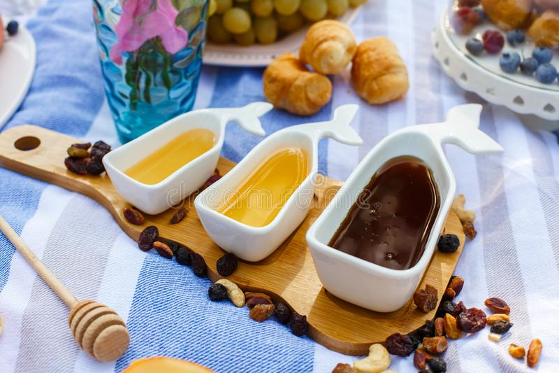 Stellen Sie von drei weißen Saucieren mit süßem Honig auf hölzernem Behälter an der Picknicknahrung ausbreiten Hintergrund ein stockbilder