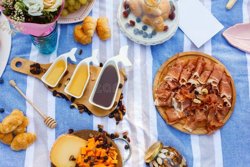 Stellen Sie von drei weißen Saucieren mit süßem Honig auf hölzernem Behälter an der Picknicknahrung ausbreiten Hintergrund ein stockbild